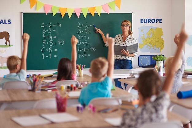 Muchas manos de voluntarios durante la clase de matemáticas.