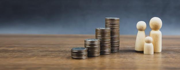 Muchas monedas se apilan en forma de gráfico con una muñeca de madera familiar para ahorrar dinero.