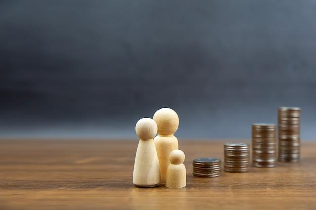 Muchas monedas se apilan en forma de gráfico con una muñeca de madera familiar para ideas de ahorro de dinero.
