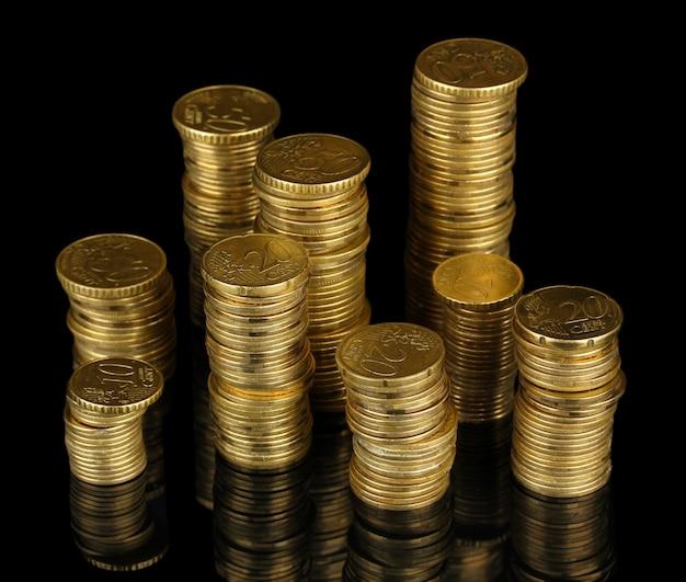 Muchas monedas en columnas aisladas en negro