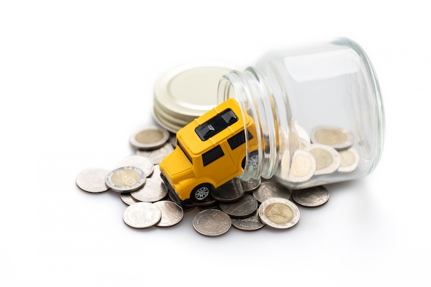 Muchas monedas en un frasco de vidrio y un carro de juguete amarillo