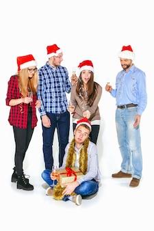 Muchas mujeres y hombres jóvenes bebiendo en la fiesta de navidad en estudio blanco
