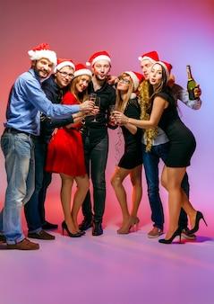 Muchas mujeres y hombres jóvenes bebiendo en la fiesta de navidad en estudio rosa