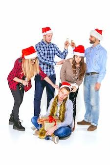 Muchas mujeres y hombres jóvenes bebiendo en la fiesta de navidad sobre fondo blanco de estudio