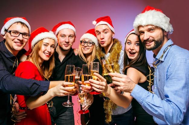 Muchas mujeres y hombres jóvenes bebiendo en la fiesta de navidad