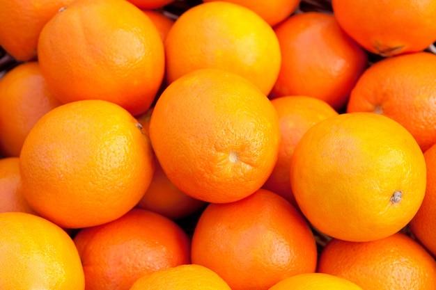 Muchas naranjas apiladas con una piel brillante