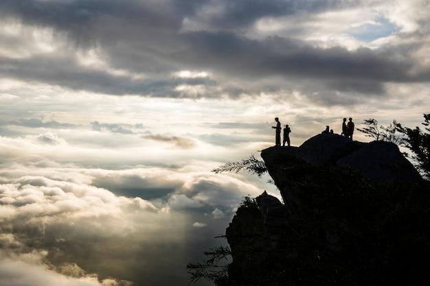 Muchas nubes en la salida del sol con la gente de silueta en la cima de la montaña