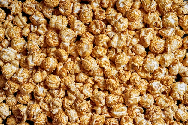 Muchas palomitas de maíz con primer plano de caramelo dulce para películas