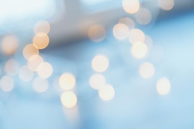 Muchas pequeñas bombillas eléctricas borrosas en una pared. luces borrosas amarillas. muro de luces navideñas