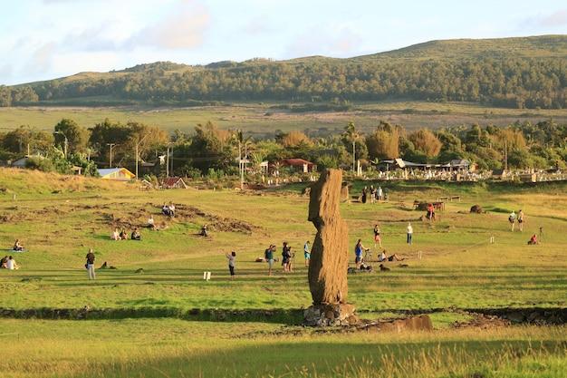 Muchas personas esperan la vista del atardecer en ahu tahai con la estatua de moai en la isla de pascua, chile