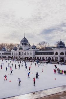 Muchas personas pasan sus vacaciones patinando en la pista de hielo de city park en budapest, hungría