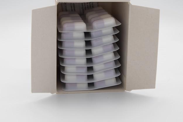 Muchas píldoras médicas en una caja en blanco