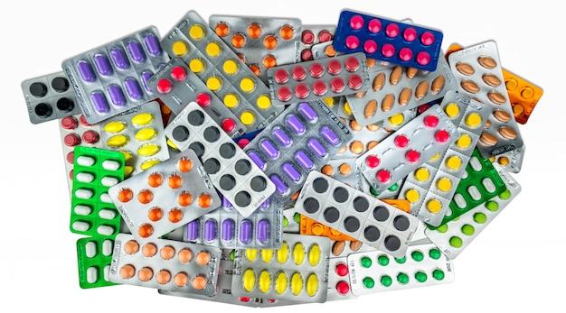 Muchas de las píldoras de la tableta aisladas en el fondo blanco. comprimidos de color amarillo, morado, negro, naranja, rosa y verde en blister. medicamento analgésico. medicamento para la migraña. industria farmacéutica.