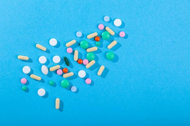 Muchas píldoras y tabletas dispersas de colores, suplementos para enfermedades, medicamentos establecidos