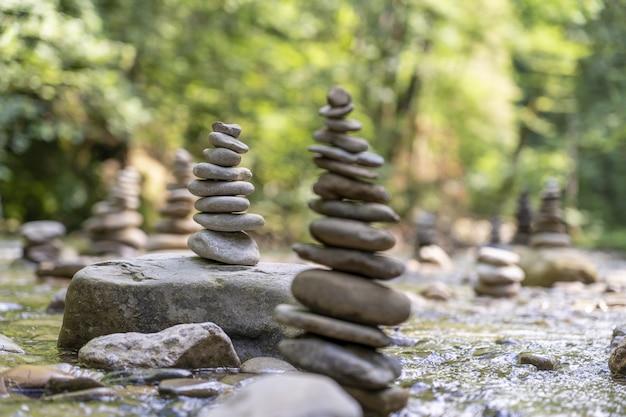 Muchas pirámides de piedra en equilibrio sobre el agua de un río