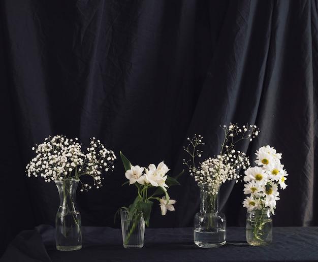 Muchas plantas verdes y flores en jarrones.