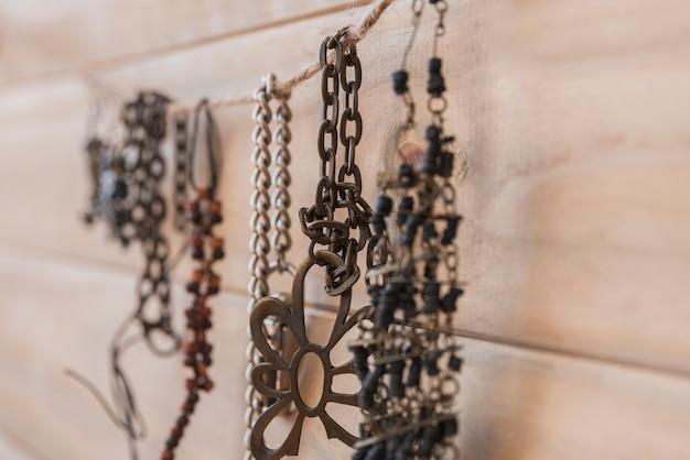Muchas pulseras metálicas colgando de una cuerda contra una pared de madera.