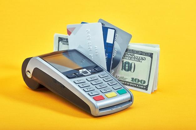 Muchas tarjetas de crédito diferentes, billetes de un dólar y terminal de pago sobre fondo amarillo, primer plano