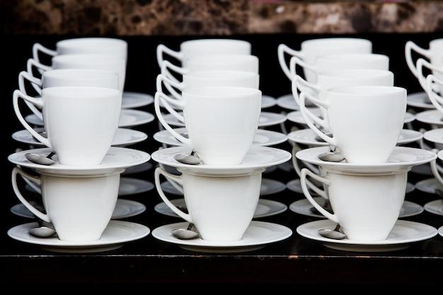Muchas tazas de café con leche en línea sobre un buffet
