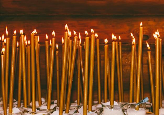 Muchas velas de cera encendidas en el templo