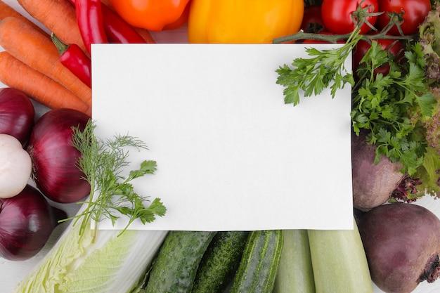 Muchas verduras diferentes con papel en blanco.