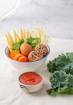Muchas verduras en un tazón blanco incluyen zanahorias, maíz tierno, hongos shiitake, agujas doradas, apio y huevos de gallina. sukiyaki y salsa.