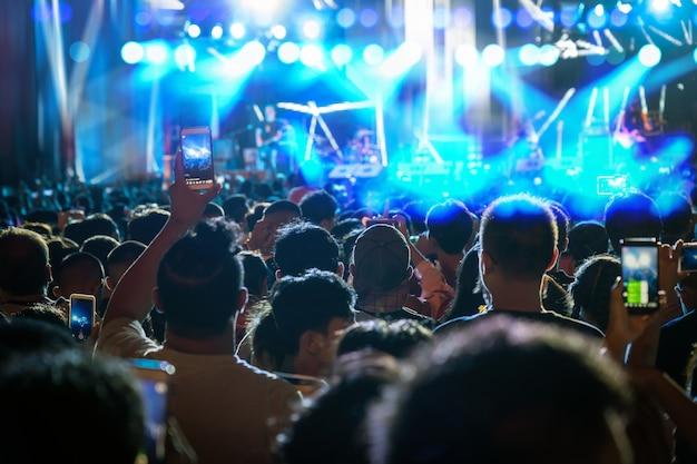Muchedumbre del concierto de la mano del club de fans de la música que sostiene el teléfono elegante móvil que toma el expediente video o vivo