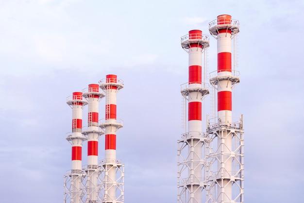 Mucho blanco con la nueva sala de calderas roja de los tubos en el cielo azul. tubería con caldera de calentamiento a vapor.
