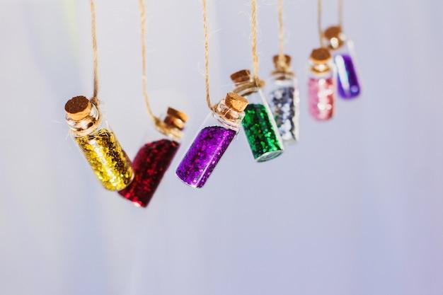 Mucho brillo en frascos de vidrio en cuerdas en una pared clara