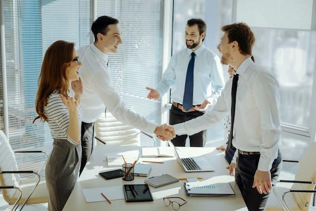 Mucho tiempo sin verte. compañeros agradables alegres dándose la mano e intercambiando sonrisas antes de comenzar la reunión de negocios