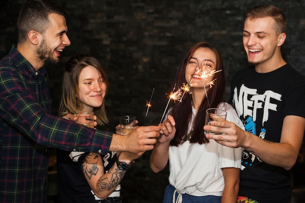 Muchos amigos felices sosteniendo bebidas iluminan la chispa