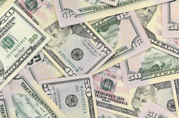 Muchos billetes de dólar estadounidense cincuenta en superficie de fondo plano de cerca. vista superior plana. concepto de negocio abstracto