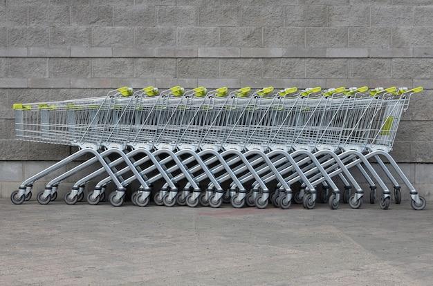 Muchos carros de supermercado con asas amarillas de pie en una fila en el centro de la foto junto al ladrillo gris del estacionamiento del supermercado.