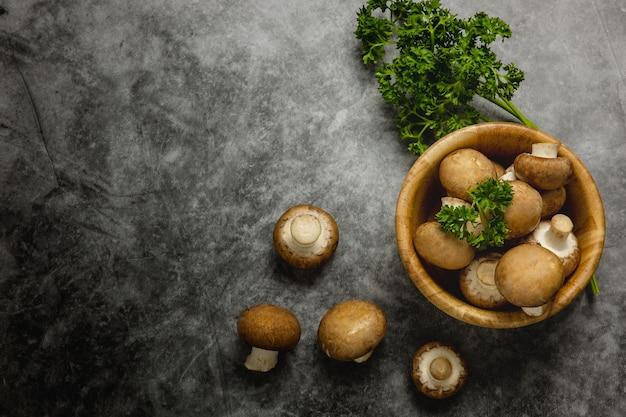 Muchos champiñones marrones en una taza de madera colocada en el piso de cemento negro las setas caen al suelo con un perejil al lado. concepto de comida sana y comida vegetariana. tono oscuro. vista superior y espacio de copia