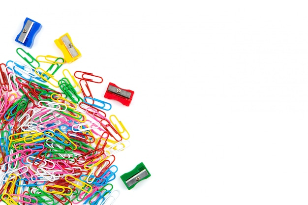 Muchos clips de papel coloreados y sacapuntas de lápiz en un fondo blanco. vista superior y espacio de copia.