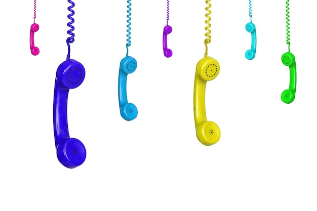Muchos coloridos teléfonos antiguos colgando aislado sobre un fondo blanco.