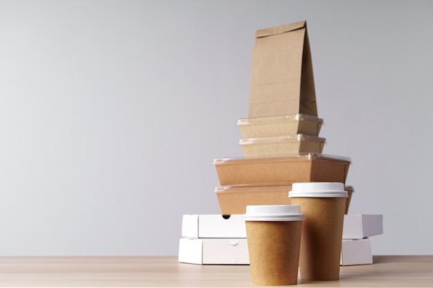 Muchos contenedores de comida para llevar, caja de pizza, tazas de café y bolsas de papel sobre fondo gris claro