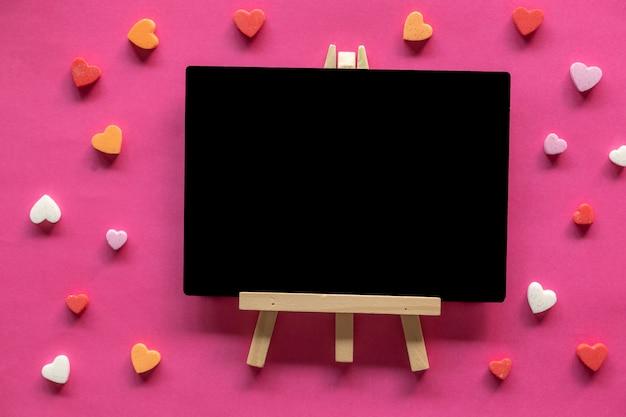 Muchos corazones alrededor de pizarra sobre fondo rosa, icono de amor, día de san valentín, concepto de relaciones