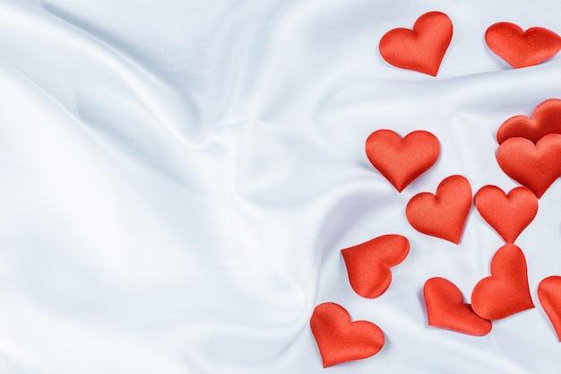Muchos corazones rojos sobre un arrugado en blanco