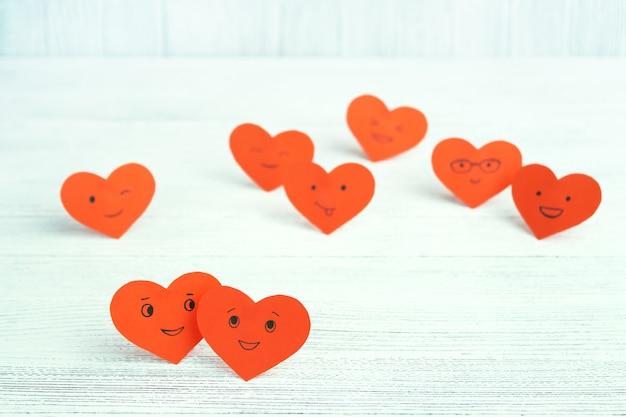 Muchos corazones rojos sonrientes en una mesa de madera clara. día de san valentín. pareja enamorada.