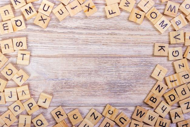 Muchos cubos de educación abc esparcidos sobre fondo de mesa de madera