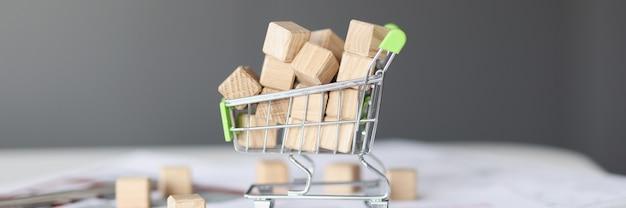Muchos cubos de madera en el concepto de construcción de viviendas de primer plano de coche de compras de juguete
