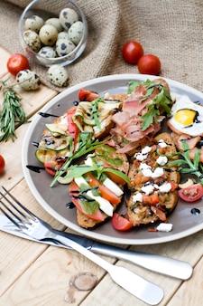 Muchos deliciosos bruschetta con queso, tomate, huevo de codorniz, jamón, salmón, verduras asadas y hierbas