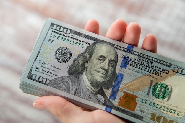 Muchos dólares cayendo en la mano de la mujer con dinero