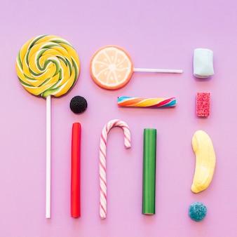 Muchos dulces gomosos, azúcar, jalea, piruletas en fondo rosado