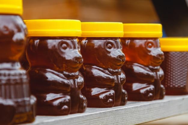 Muchos frascos con miel orgánica fresca en el mercado agrícola.