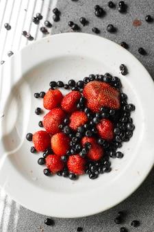 Muchos jugosos frutos rojos maduros y moras se encuentran en una placa de cerámica blanca sobre la mesa