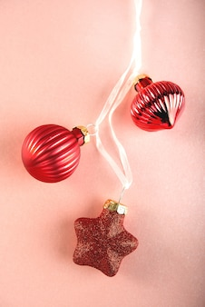 Muchos juguetes de árbol de navidad rojo sobre rosa