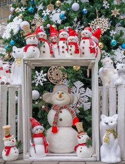 Muchos juguetes muñecos de nieve, ciervos, osos y zorros, de pie bajo el árbol, juguetes de navidad,