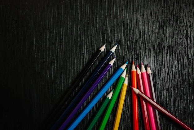 Muchos lápices de colores sobre un fondo negro. nuevos lapices